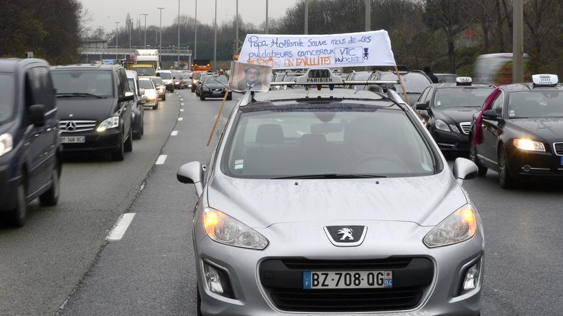 Pariser Taxifahrer blockieren am 15. Dezember 2014 den Verkehr auf einer Straße bei Paris, um gegen den US-Fahrdienst UberPop zu demonstrieren.