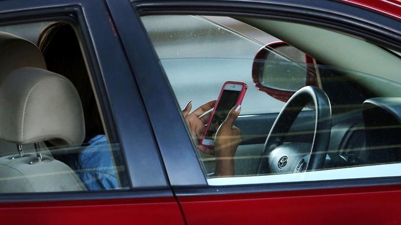 Autofahren: Autofahrer, die am Lenkrad ihr Smartphone bedienen, sind ein Verkehrsrisiko.