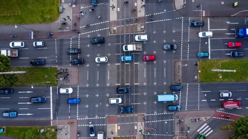 Öffentlicher Nahverkehr: Kreuzung mit Straßenbahnschienen und Kraftfahrzeugen in Köln: Die Preise für den öffentlichen Nahverkehr sind stärker gestiegen als für Autofahrerinnen und Autofahrer.