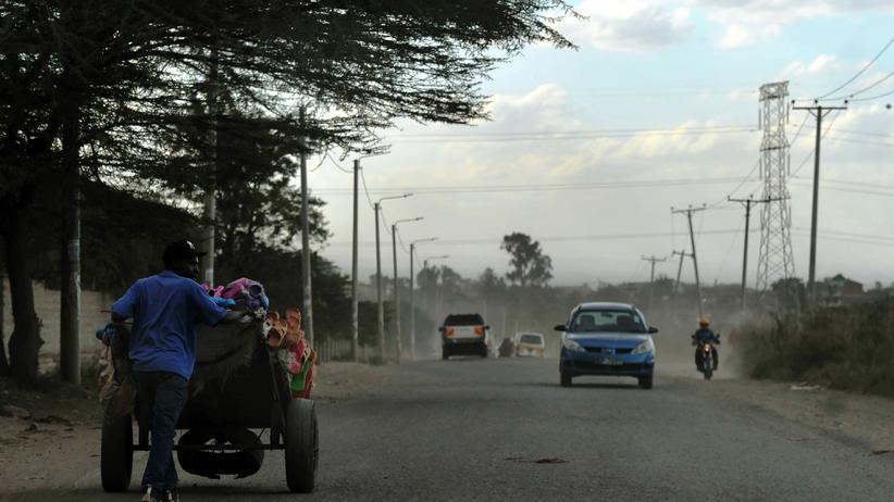 Verkehrswende: Ein Sandalenverkäufer in Nairobi, Kenia, schiebt seinen Handkarren eine Straße entlang