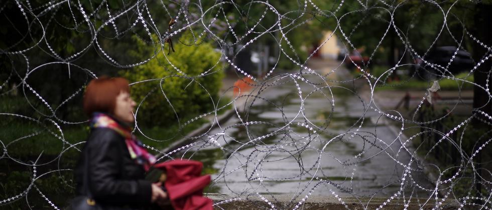 Eine Frau geht an einem Gebäude der Donezker Regionalregierung vorbei, Mai 2014