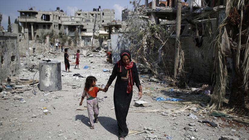 Eine Mutter läuft mit ihrem Kind durch die Ruinen von Beit Hanoum im Gazastreifen.