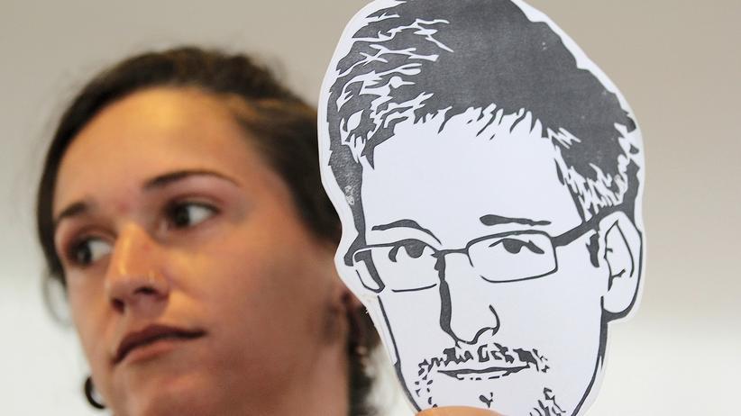 Eine Aktivistin mit einer Maske Edward Snowdens