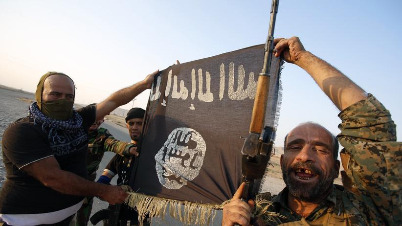 """Irak: Zwei Männer halten eine Flagge des """"Islamischen Staates"""" (Archiv)"""