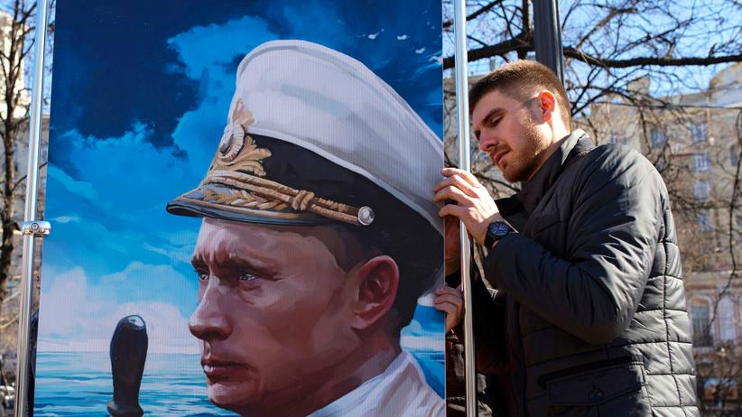 Russland: A man places a picture depicting Russia's President Vladimir Putin in a navy uniform at an open-air political cartoons exhibition dedicated to the one-year anniversary of Crimea voting to leave Ukraine and join the Russian state in central Moscow on March 16, 2015.
