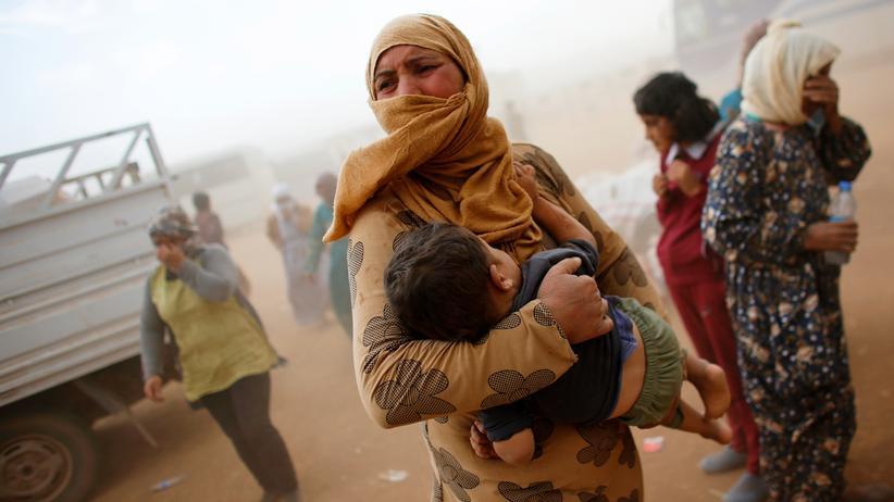 Syrische Flüchtlinge warten auf einen Hilfstransport.
