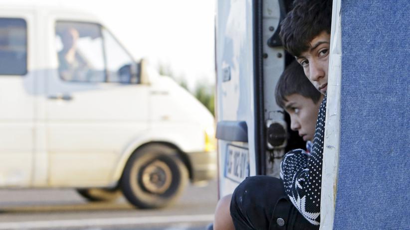 Flüchtlinge: Zwei geflüchtete Jungs gucken aus einem Bus, den die ungarische Polizei in der Nähe des Grenzortes Gyor herausgewunken hat.