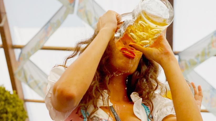 Junge Frau trinkt Bier auf dem Oktoberfest in München
