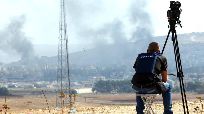 Terrorwarnungen: Ein Kameramann beobachtet an der türkisch-syrischen Grenze die Kämpfe im nahe gelegenen Kobane.