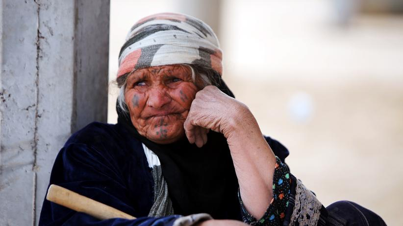 Naher Osten: An Iraqi Sunni woman sits outside her home in the village of Albu Ajil, east of the northern Iraqi city of Tikrit, on March 8, 2015 as Shiite fighters and members of Iraq's Popular Mobilisation units supporting the government forces in the battle against the Islamic State (IS) group take part in a military operation to regain control of the Tikrit area. Some 30,000 Iraqi security forces members and allied fighters launched an operation to retake Tikrit at the beginning of March, the largest of its kind since IS group forces overran swathes of territory in June. AFP PHOTO / AHMAD AL-RUBAYE (Photo credit should read AHMAD AL-RUBAYE/AFP/Getty Images)