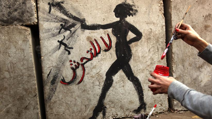 """Arabische Gesellschaften: Eine ägyptische Aktivistin malt ein Graffiti an eine Hauswand in Kairo. Auf Arabisch steht dort: """"Nein zu sexueller Gewalt""""."""