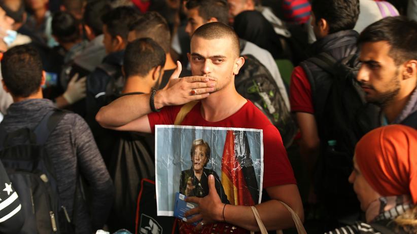 Flüchtlingspolitik: Ein syrischer Flüchtling mit Kanzlerinnen-Foto am Münchner Hauptbahnhof