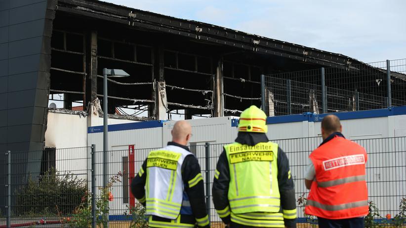 Feuerwehrmänner und Sanitäter stehen vor der ausgebrannten Turnhalle in Nauen.