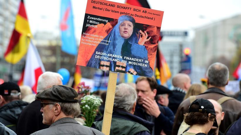 Alternative für Deutschland: Ein AfD-Anhänger hält bei einer Demonstration in Berlin ein Plakat, das Kanzlerin Merkel in einer Burka zeigt. (Bild vom 7. November 2015)
