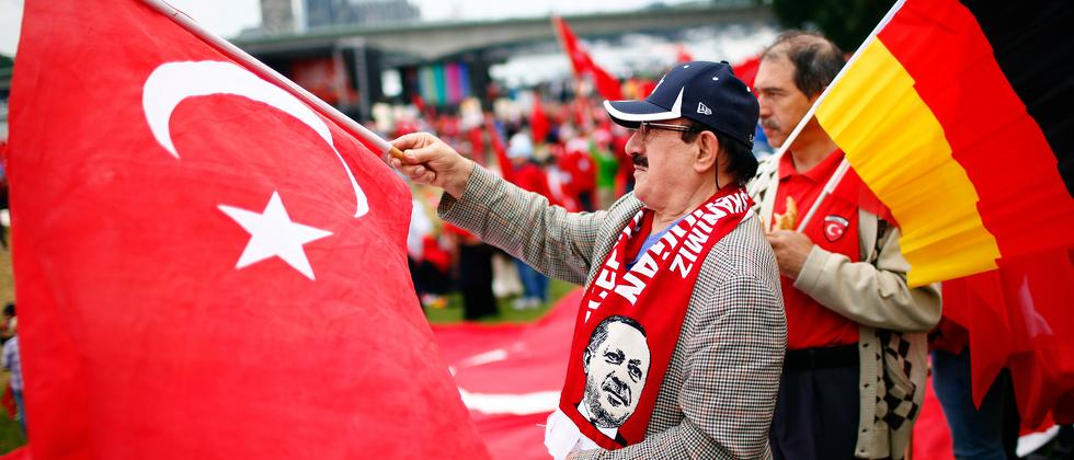 Unterstützer Erdoğans schwenken bei der Demonstration in Köln die türkische Flagge.