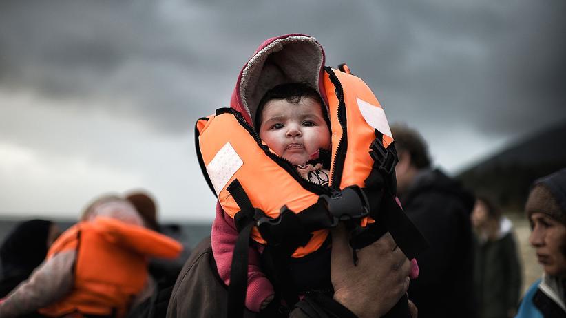 Deutsche Flüchtlingspolitik: Ein Mann hält sein Baby bei der Ankunft auf Lesbos