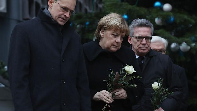 Emotionen: Der Berliner Bürgermeister Michael Müller, Bundeskanzlerin Angela Merkel und Bundesinnenminister Thomas de Maizière legen einen Tag nach dem Berliner Anschlag Blumen am Breitscheidplatz nieder.