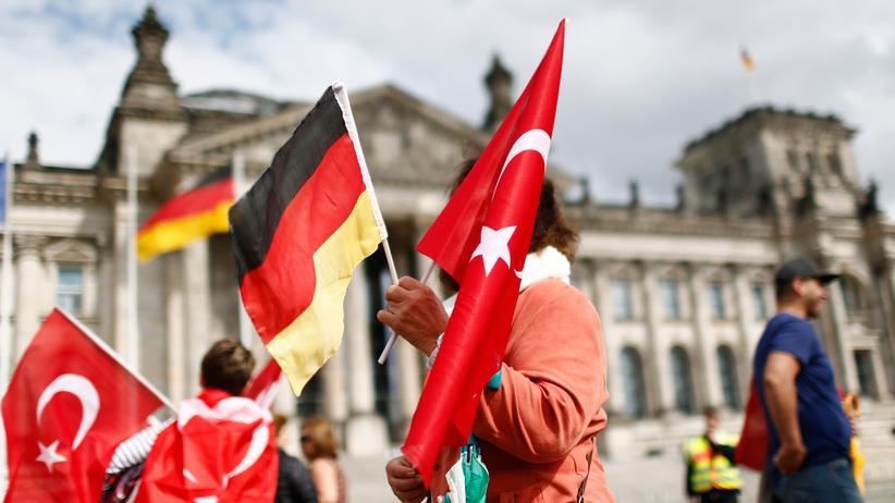 Doppelpass: Demonstrantin mit deutscher und türkischer Fahne vor dem Reichtagsgebäude