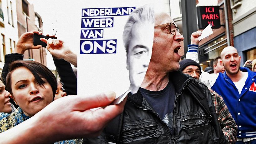 Niederlande: Streit um die Einwanderung: Während einer Pro-Einwanderungs-Demonstration in Heerlen hatten Unterstützer von Geert Wilders (im Hintergrund) den beiden Demonstranten im Vordergrund ihre Banner entrissen. Jetzt hält ein Anhänger von Wilders das Porträt des Politikers in die Kamera.