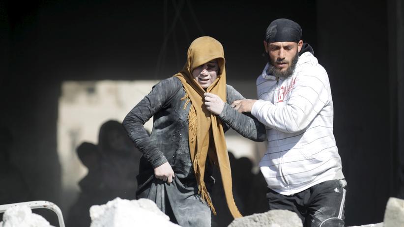 Flüchtlinge: Ein Mann hilft einer Frau nach einem Luftangriff in der syrischen Provinz Idlib.