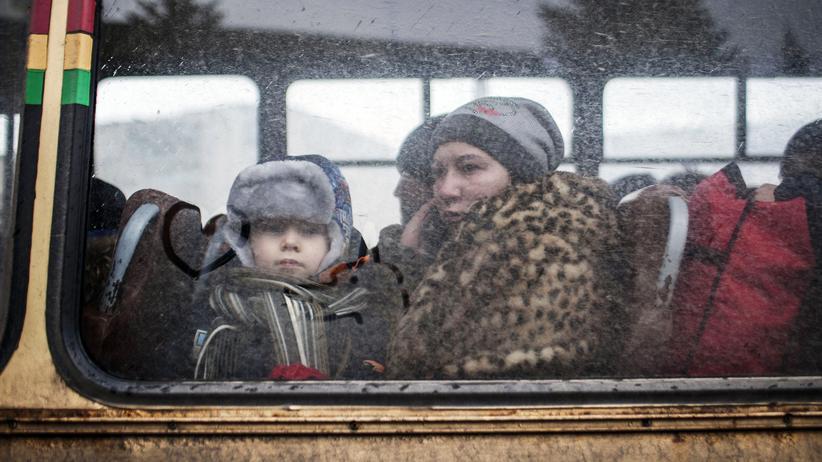 Internationaler Gerichtshof: Eine Frau und ein kleiner Junge sitzen in der Ostukraine in einem Bus für Flüchtlinge.