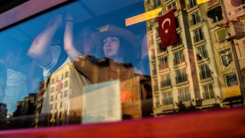 Deutsch-türkische Beziehungen: Eine Frau betrachtet in der Straßenbahn in Istanbul die türkischen Flaggen vorm Fenster.