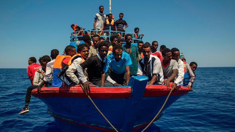 Mittelmeer: Flüchtlinge auf einem Boot im Mittelmeer warten auf ein Rettungsboot um an die libysche Küste gebracht zu werden.