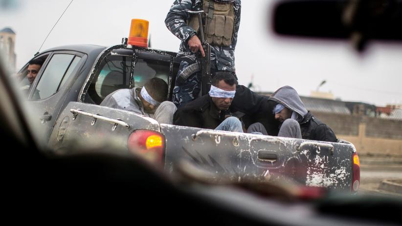 """Innere Sicherheit: Kämpfer der christlichen Miliz Nineveh Plain Protection Units (NPU) transportieren im Dezember 2016 in Mossul vier Mitglieder der Terrormiliz """"Islamischer Staat"""" in einem Auto."""