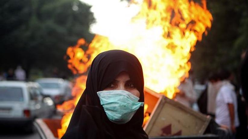 Iranische Revolution: Eine Demonstrantin vor einem brennenden Müllcontainer am 9. Juli 2009 in Teheran. Die Proteste fanden in Erinnerung an die blutigen Studentenunruhen von 1999 statt.