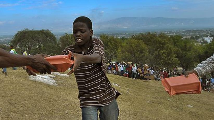 In einem Flüchtlingslager in Port-au-Prince werden Nahrungsmittel verteilt