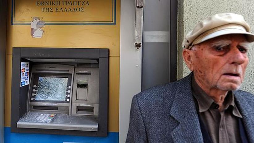 Älterer griechischer Mann vor einem zerstörten Geldautomaten in Athen