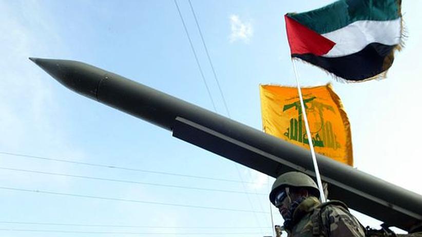 Eine Parade der Hisbollah im Libanon. Im Hintergrund die Flagge der Organisation, rechts die Palästinas