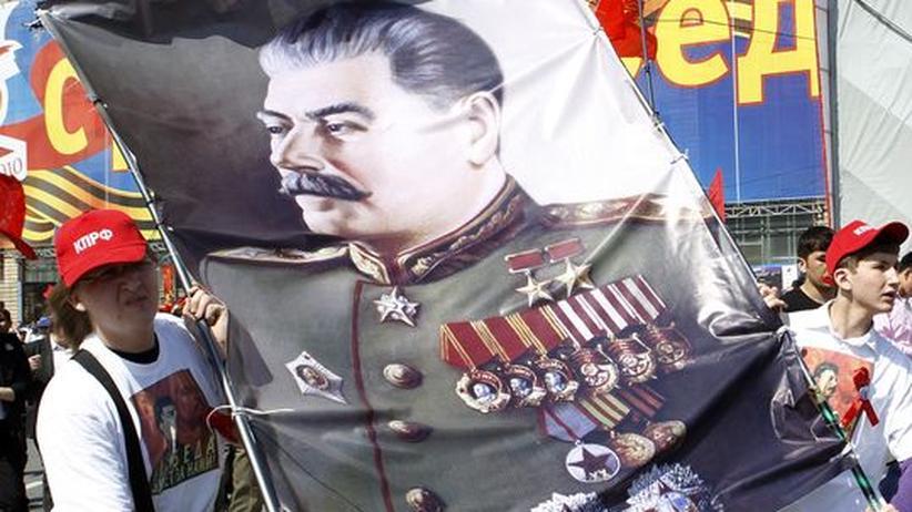 Ein russischer Kommunist marschiert mit einem Stalin-Bild durch die Moskauer Innenstadt