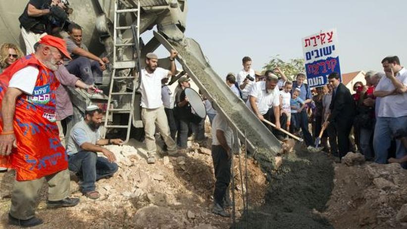 Nach dem Baustop: Israelische Siedler stehen um einen Cement- Mixer herum