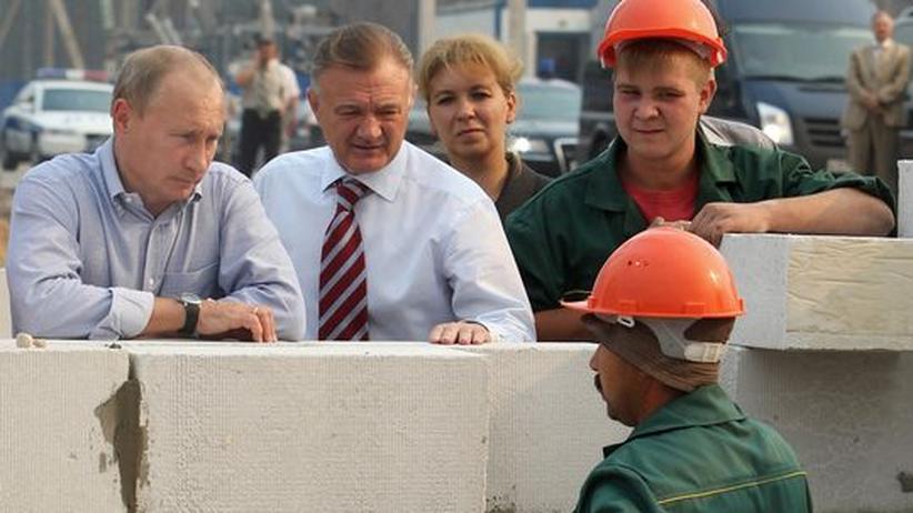Russlands Premierminister Wladimir Putin spricht mit Arbeitern in einer von den Waldbränden vernichteten Siedlung.