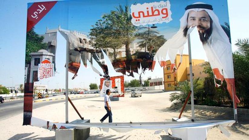 Ein Mann laeuft an Plakaten in Manama vorbei, die für die Parlamentswahl am Samstag werben