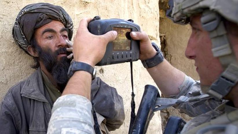 Ausblick: Ein amerikanischer Soldat fotografiert einen afghanischen Dorfbewohner bei einer Razzia