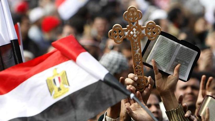 Kopten und Muslime halten während der Proteste in Kairo ein Kreuz und einen Koran hoch