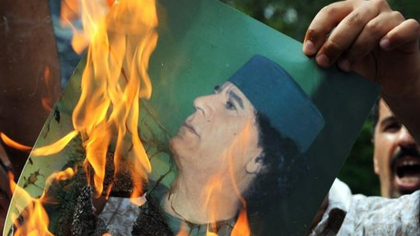 Demonstranten entzünden ein Poster von Muammar al-Gadhafi