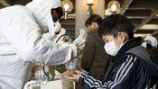 Eine Hilfskraft überprüft die Strahlenwerte eines Jungen in Koriyama, circa 60 Kilometer entfernt von Fukushima.