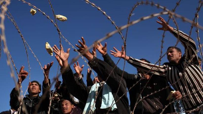 Sanktionen: Libysche Flüchtlinge warten an der Grenze zu Tunesien, während ihnen Nahrungsmittel zugeworfen werden
