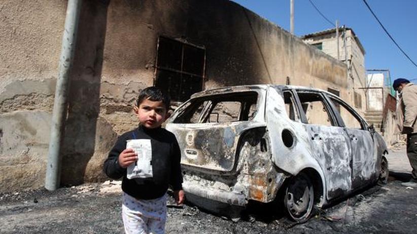 Nahost-Konflikt: Ein Junge steht vor einem ausgebrannten Auto in der palästinensichen Stadt Jinsafot. Israelische Siedler hatten das Auto in der Nacht zuvor angezündet
