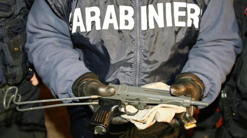 Ein italienischer Carabinieri präsentiert die Maschinenpistole eines Mafia-Führers.