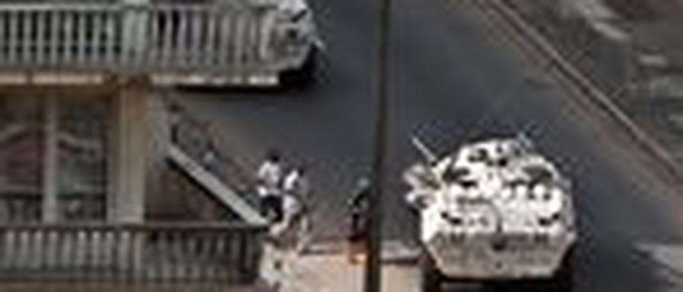 Zivilisten werden in Abidjan mit einem gepanzerten Fahrzeug der UN in Sicherheit gebracht.
