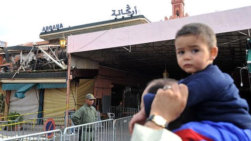 Autor Tahar Ben Jelloun: Ein Mann und sein Sohn blicken auf die Überreste des zerstörten Cafes in Marrakesch.