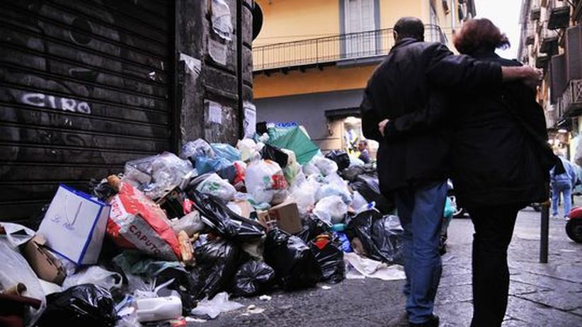 Italien: Ein Pärchen läuft vorbei an Müllbergen, die sich in den Straßen Neapels auftürmen.