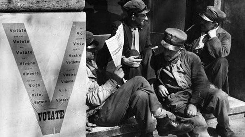 Italien: Frühjahr 1948: Italienische Arbeiter sitzen vor einem Wahlplakat.
