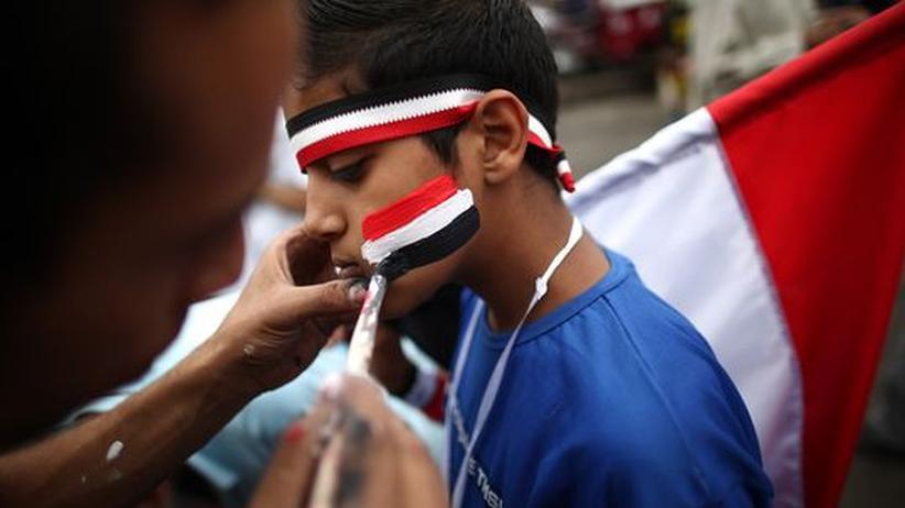 Arabische Umbrüche: Ein junger Demonstrant bekommt auf dem Tahrir-Platz in Kairo die ägyptische Flagge aufgemalt.