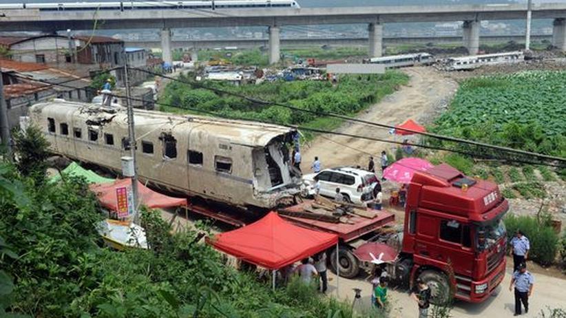 China: Die Überreste des kollidierten Zuges werden abtransportiert.