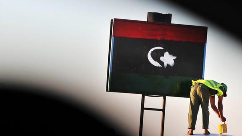 Libyen: Ein Mann malt die libysche Flagge über eine Plakatwerbung.